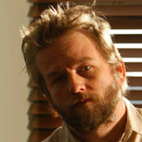 Miles Fiedler played by Dallas Roberts