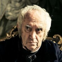 Sir Stuart Strange played by Jonathan Pryce
